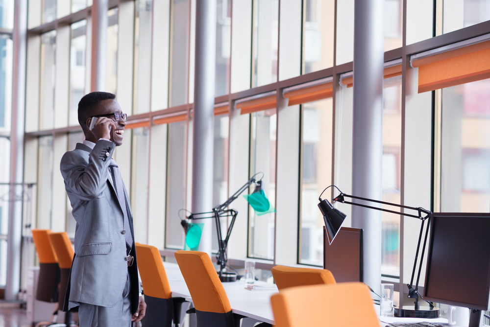 Happy smiling successful African American businessman  in a suit in a modern bright office indoors speel on phone
